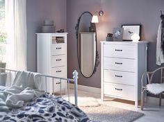 Ein Schlafzimmer mit zwei BRUSALI Kommoden mit 4 Schubladen in Weiß ‒ einmal niedrig, einmal hoch ‒ und ovalem EKNE Spiegel
