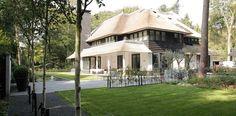 Villa met rieten kap en veranda.