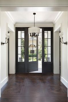 A black front door flanked by sidelights opens to intricate parquet wood floors leading past doorways to an oil rubbed bronze chandelier flanked by oil rubbed bronze sconces. French Doors With Sidelights, Exterior Doors With Sidelights, Windows And Doors, Big Windows, Black Exterior Doors, Black Front Doors, Front French Doors, Colonial Front Door, Double Front Doors