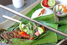 Kerapu Bakar Bambu, delicious grilled grouper fish cooked in bamboo wrapper, served with steamed rice and exquisite varieties of chili; sambal bakar and sambal tomat.