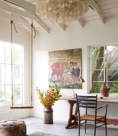 A swing, along with a pastoral oil painting, adds some warmth and whimsy to this California bungalow's all-white office space.