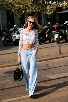 Womenswear Street Style by Ángel Robles. Fashion Photography from Milan Fashion Week. Woman wearing white lace cropped top and high waisted blue pastel trousers. On the street, Corso Sempione, Milano.
