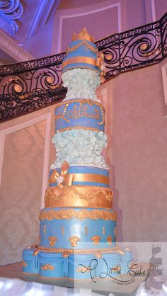Have a look at this gorgeous 11 tier birthday cake iced with royal blue fondant & decorated with gold modeling chocolate filigree. It has 2 gold bows & broaches, At top it has a golden crown.