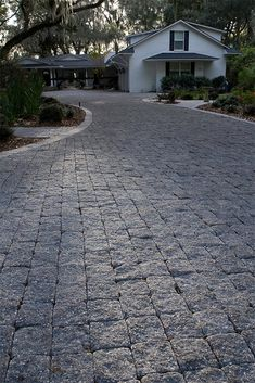 A unique split-faced, tumbled paver mimicking granite cobbles with an exposed aggregate and black granite-like finish. Tuscany offers panache and elegance and is often the paver of choice for high-end entryways and streetscapes. Driveway Design, Driveway Landscaping, Backyard Pavers, Paver Walkway, Concrete Driveways, Front Garden Landscape, Landscape Plans, Cobblestone Driveway, Myconos