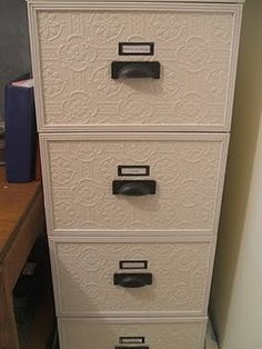 SO Clever! Dress up a horrible metal filing cabinet with Textured Wall Paper, Trim, and Better Hardware. YES!!!