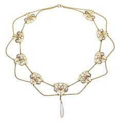 An Art Nouveau freshwater pearl necklace, circa 1890, designed as a series of nine openwork shield-shaped panels accented by circular-shaped blister pearls, each separated by an intricate twin-line gold chain, the front of the necklace suspending a Mississippi pearl pendant, pearls untested for natural origin, mounted in 15 carat yellow gold