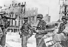 A machine gun squad has halted in a main street in the heart of Stalingrad. One of the soldiers can clearly be seen holding a captured map, probably of the city. Although this area of Stalingrad had been captured, moving through it was still perilous. A great many of the approaches into the city were still heavily mined and sappers would often lay in wait.