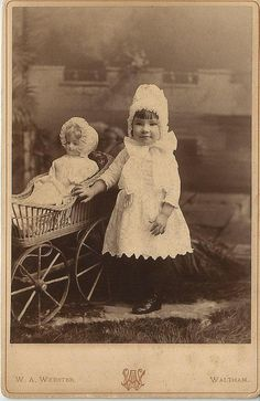Circa 1890 little girl and her doll look exactly alike. Antique photograph, American image.