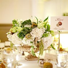 This is more rustic,using a vintage urn filled with white hydrangeas,kale,green amaranthus,and kiwi.