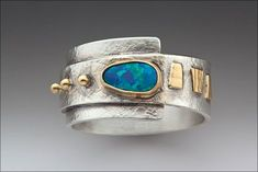 """Wrap Around It by Linda Lewis Materials: Opal, sterling silver and 22k gold Dimensions: 1/2"""" X 1"""" Hand fabricated from sterling sheet and textured with handmade paper using gold accents."""