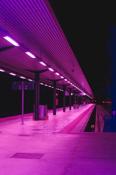 Neon pink lights at a train station, vaporwave aesthetic.