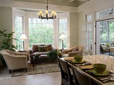 Kitchen extends to seating area with bay window; French doors open to screened porch (or patio).