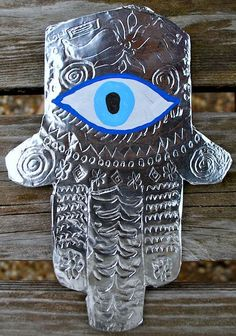 Hamsa Multicultural Craft from the Middle East- easy and stunning for kids! The hamsa is a hand-shaped amulet found throughout the Middle East, used as a decoration by Jewish, Muslim, and Christian people. Hamsas can be found on the entrances in homes or hanging in cars because of the superstition that they ward off the evil eye and protect people around them.