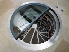 COOL UNDERGROUND SPIRAL STAIRCASE GOES DOWN TO STACKS OF WINE BOTTLES ARRANGED ON CIRCULAR SHELVES. CLEAR GLASS COVER OPENS TO REVEAL ENTRY TO THIS UNIQUE WINE-CELLAR!