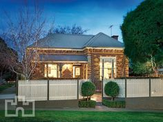 Brick victorian house exterior with picket fence & hedging - House Facade photo 237318