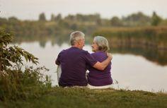 Happy couple sitting beside a lake