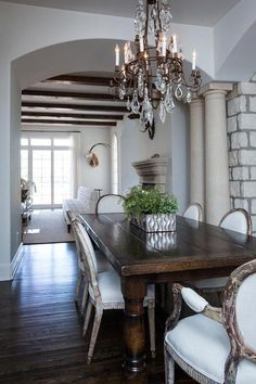 French dining room boasts a crystal chandelier illuminating a dark wood dining table lined with gray linen French dining chairs alongside doric columns.