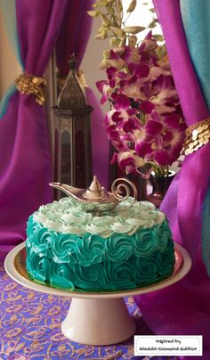 A teal Princess Jasmine and Genie-inspired cake topped with Aladdin's Lamp – perfect for an Arabian Nights theme party. Inspired by Disney's Aladdin Diamond Edition. Now on Blu-ray™, Digital HD & Disney Movies Anywhere.