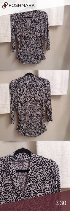 Vince Camuto 3/4 Sleeve Top This gorgeous!! Black & white animal print v-neck top has ruching on both bottom sides and is 95% Polyester/5% Spandex.  The chest measures 41 inches and the length is 28 inches. Excellent condition!! Vince Camuto Tops