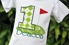 Custom bodysuit or tshirt with an applique number and flag atop a golf green, each in your choice of fabric, and your childs first name. Link