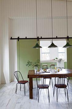 Comedor rústico con detalle de puerta corrediza en verde musgo y revestimiento de machimbre blanco, en una casa de Costa Esmeralda.