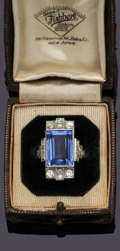 An Art Deco style diamond and blue paste dress ring The rectangular paste stone with old-cut diamond set detail to both sides, between diamond set stepped shoulders, to shank stamped 'platinum', ring size N½.