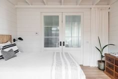 """Roberto Sosa Beach House Bedroom Above: In a bedroom, white curtains pull across double sliding doors for added privacy. The natural-fiber headboard is a """"very old West Elm"""" find, the Henslers say."""