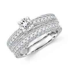 This gorgeous bridal set features round diamond with stones surrounded on sides crafted in 14K white gold.