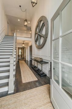 Two-story foyer with full wall wainscoting, jute rugs and rustic dark wood floors | Vintage South Development