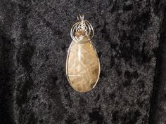 Large Petoskey Stone wrapped in sterling silver square wire. Can purchase at World of Rocks in Ypsilanti, MI. This has been sold thanks for looking.