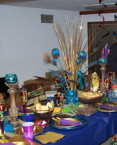A Royal Egyptian Feast table setting - my table at 2012 Mardi Gras event.  Peacock feathered balls, peacock feather sprigs, gold grass, teal votive cups, chargers from Hobby Lobby.  Glassware and beaded boxes from Pier 1.  Rattan baskets from Walmart.  Centerpiece vase filled with teal garland and fairy battery-operated lights.
