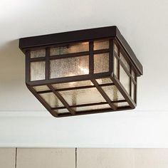 Inspired by classic American Arts and Crafts style, this Kathy Ireland ceiling light shines with clear seedy glass.