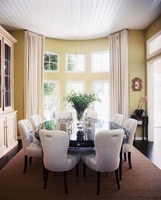 Traditional Photo - Green walls accented by white curtains, tufted chairs, and a wood table