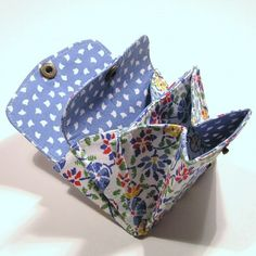 This is a small change purse with three sections and two flaps that snap shut. There are red, yellow and blue flowers on a white background on the outside and it is lined with a blue and white print.    It measures only 3 1/2-inches (8.9 cm) high and 4 1/4-inches (10.8 cm) wide and is easy to fit in your pocket or purse.  8 bucks    https://www.facebook.com/pages/Shastababy/164993571710