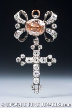 A very fine 18th century old cut diamond cross pendant, designed as a diamond bow, centered by a large oval Cognac coloured diamond, suspending a diamond cross, mounted in silver and gold. On a black velvet ribbon.Late 18th century
