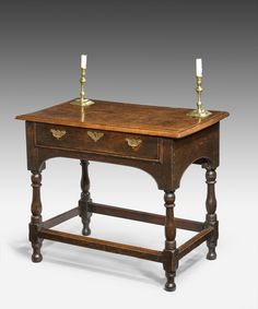 A Jacobean oak side table. An elegant late Seventeenth Century Jacobean oak side table; the single frieze drawer which retains its original handles within an arched frieze and raised on turned legs united by stretchers.