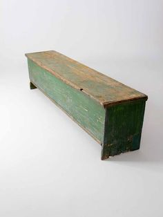 circa early 20th century This is an antique primitive wood trunk bench. Rustic, painted green wood shapes the long bench. Large iron hinges open the seat to a single compartment interior. - hinge top