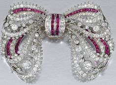 A RUBY AND DIAMOND BROOCH, Ca. 1910.  Designed as a stylised tied ribbon bow, decorated with open work floral motifs and millegrain set with circular- and rose-cut diamonds and calibré-cut rubies.