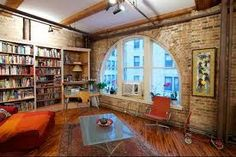 lofts: This is a Chicago loft. Love the shape and size of the window, not to mention the floors, bookcases, and orange.