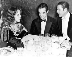 This photograph shows Howard Hughes (center) with Helen Gilbert and Errol Flynn seated at table for charity Christmas party, Beverly Hills, ...