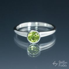 Tapered bezel ring with 5mm peridot in sterling silver.. Other stones and metal options available.  Check out this item in my Etsy shop https://www.etsy.com/ca/listing/259990179/green-peridot-bezel-ring-in-modern