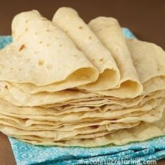 Best Ever Homemade Flour toritillas on a turquoise and white dish towel.