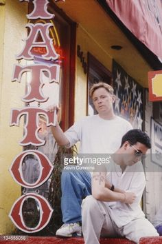 Bernard Sumner (left) and Johnny Marr, of British dance music duo Electronic, outside a tattoo parlour on Sunset Strip, Los Angeles, USA, August 1990. Marr has a tattoo drawn on to his arm reading 'Ex-Smith '82 to '87' in reference to his former band The Smiths.