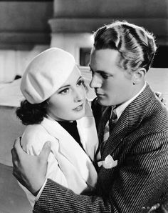 Check out this image from TCM.   Medium shot of Barbara Stanwyck as Carolyn Martin, wearing hat, and Gene Raymond as Michael Martin, embracing.