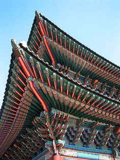 """Gyeongbok Palace, Seoul, Korea. These traditional roofs have ornate designs are called Dancheong, which refers to Korean traditional decorative coloring on wooden buildings and artifacts for the purpose of style. It literally means """"cinnabar and blue-green"""" in Korean. Applying dancheong on the surfaces of buildings require trained skills, and artisans called dancheongjang (단청장) designed the painted patterns."""