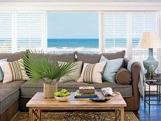 Light wall colors and wide windows make this small condo living room appear much larger. The light blue color of the walls and accent pillows play off of the ocean view, bringing the outside in. (Photo: Dominique Vorillon)