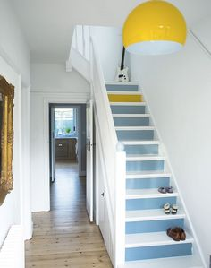 White hallway with painted stairs. Yellow lamp and one yellow step, looks nice :)