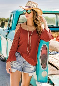 Big Country | Explore your style options in our crochet inset cold shoulder top and distressed jean shorts. A straw cowboy hat, mirrored sunglasses and long layered necklace bring rustic edge to this look.