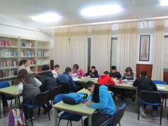 Alumnos trabajando con libros.
