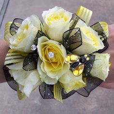 This yellow rose wrist corsage was accented with a shire black ribbon and rhinestones for a high school prom.